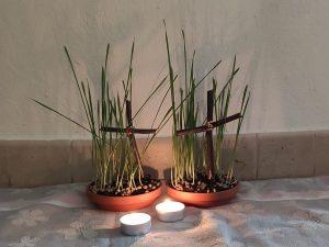 Getreidesprößlinge mit Kreuz und Teelichten